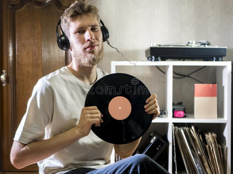 Young man sitting in cozy living room holding the vinyl record disk near records rack on the floor. Young man sitting in cozy living room holding the vinyl royalty free stock image
