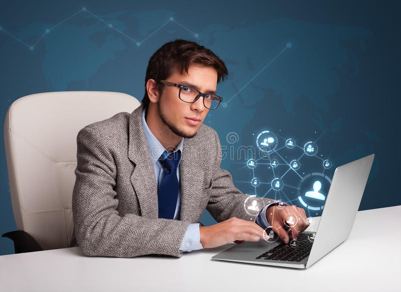 Young man sitting at desk and typing on laptop with social netwo