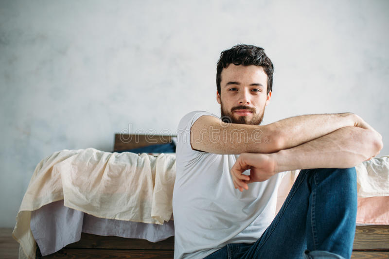 Young man sitting down on the floor near the bed stock photography