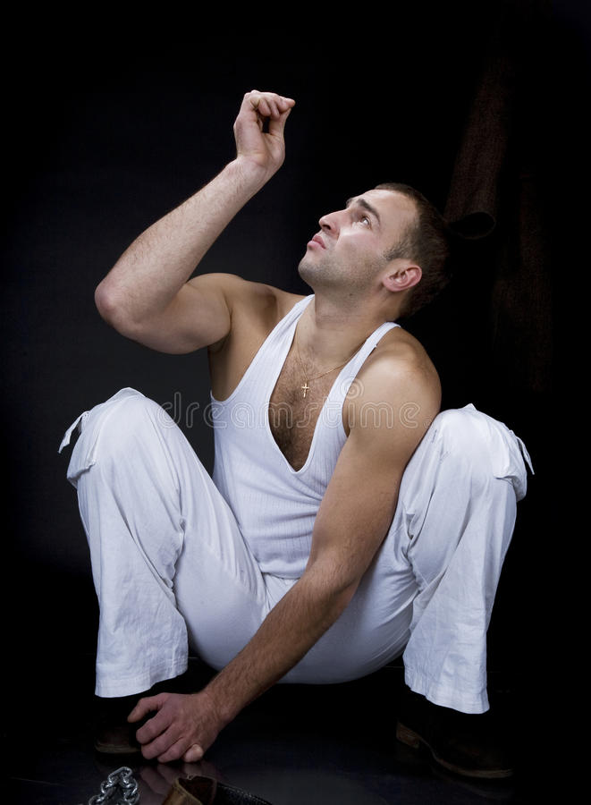 A young man sitting on the floor. And that it tells royalty free stock image