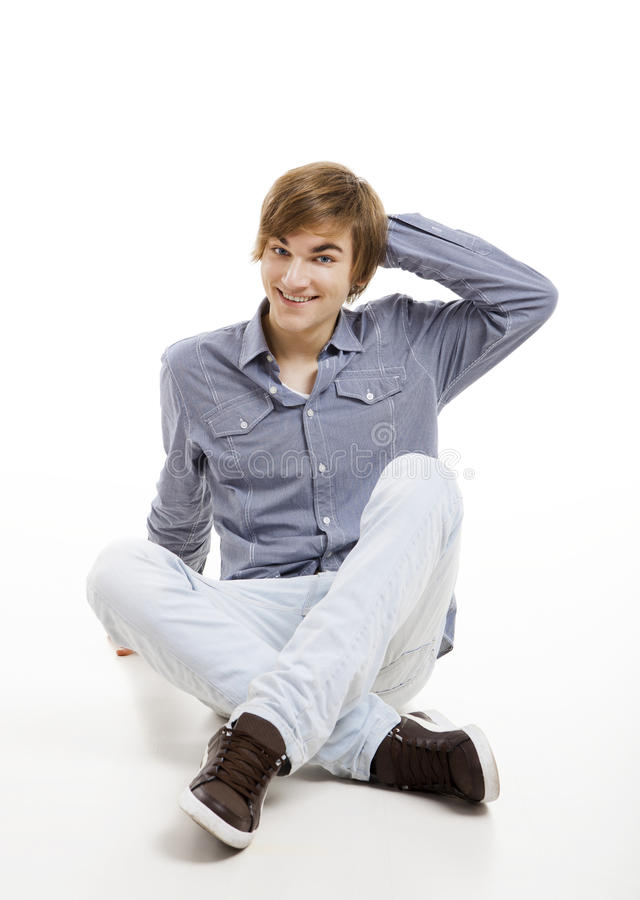 Young man sitting on the floor. Happy young man sitting on the floor, over a white background stock photo