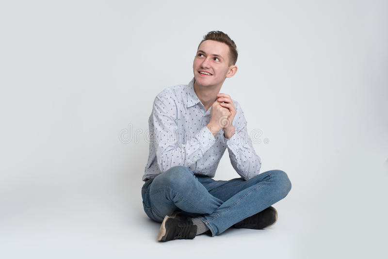 Young man sitting on the floor isolated stock photo