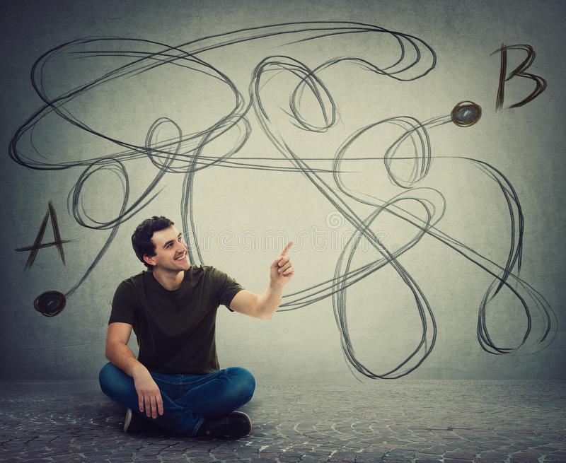 Young man sitting on the floor pointing forefinger finding the correct way from point A to point B. Solving problem, find solution royalty free stock image