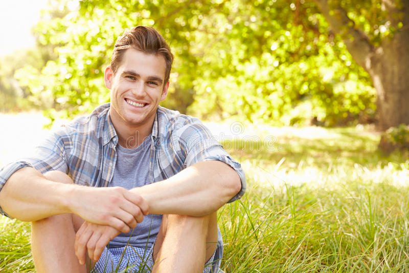 Young man sitting on grass relaxing royalty free stock image
