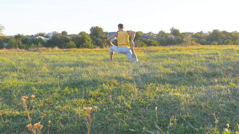 Young man sitting at green grass in the meadow and doing yoga exercise. Muscular guy stretching his body at nature stock photos