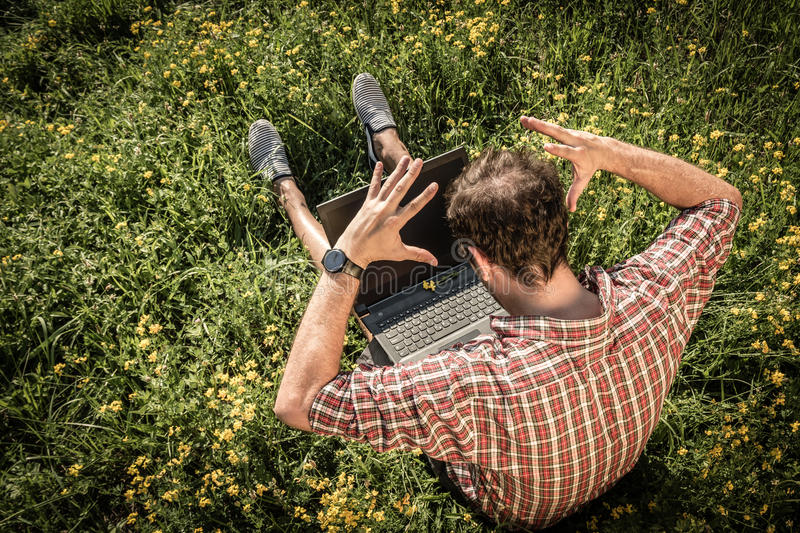 Young man sitting on green grass, upset as something is wrong wi stock photos