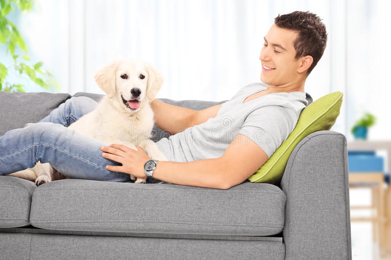 Young Man Sitting With His Puppy On A Sofa At Home Stock Photo