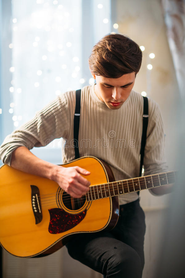 Young man sitting at home and playing guitar dramatic stock photography