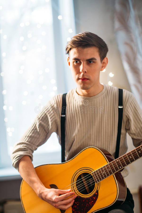Young man sitting at home and playing guitar dramatic royalty free stock photo