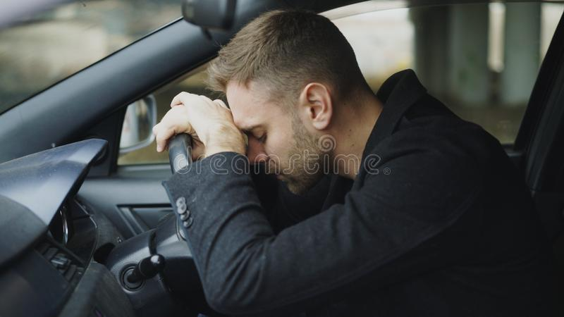Young man sitting inside car is very upset and stressed royalty free stock photo