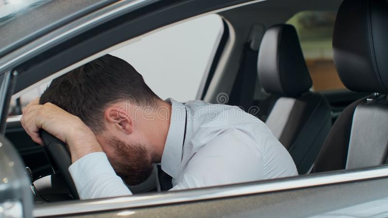 Young man sitting inside car is very upset and stressed. stock image