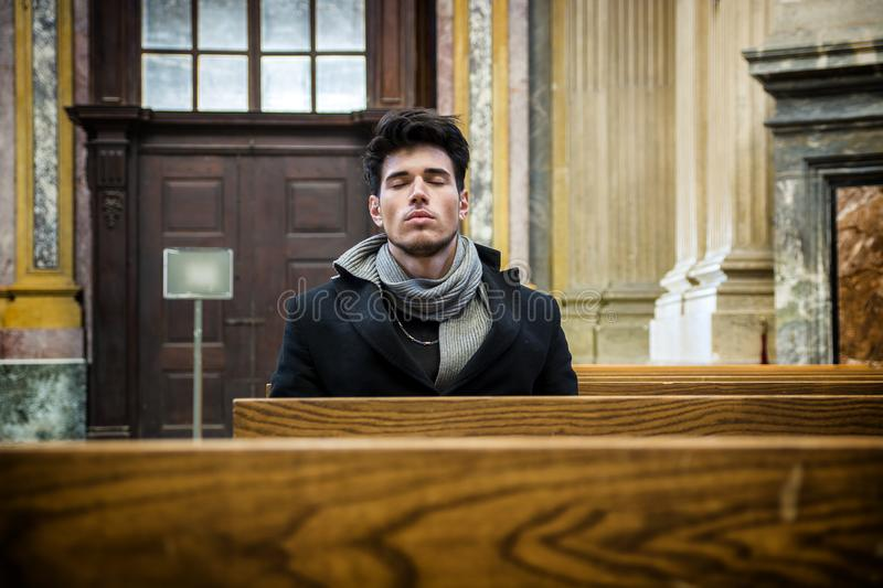 Young man sitting and kneeling praying in church. Young man sitting and kneeling in church praying, on wood bench royalty free stock photos