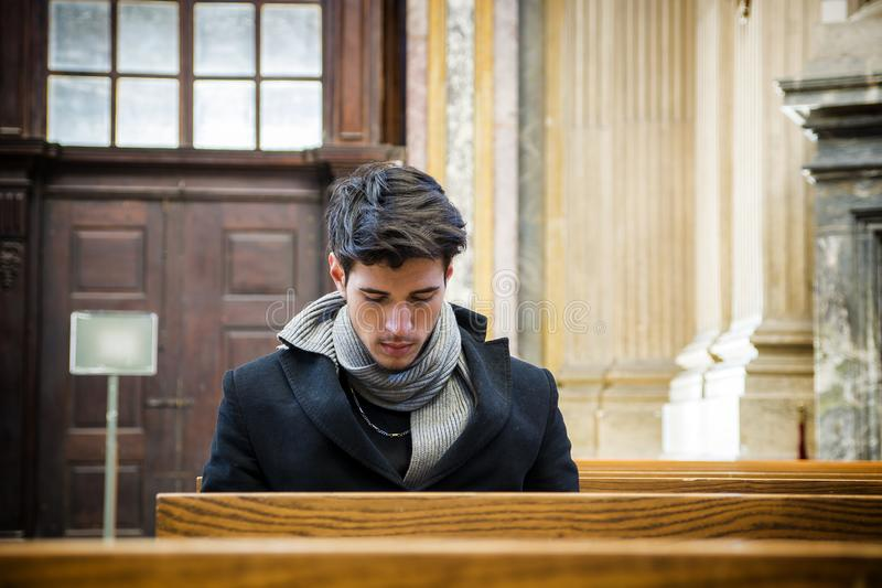 Young man sitting and kneeling praying in church. Young man sitting and kneeling in church praying, on wood bench stock image