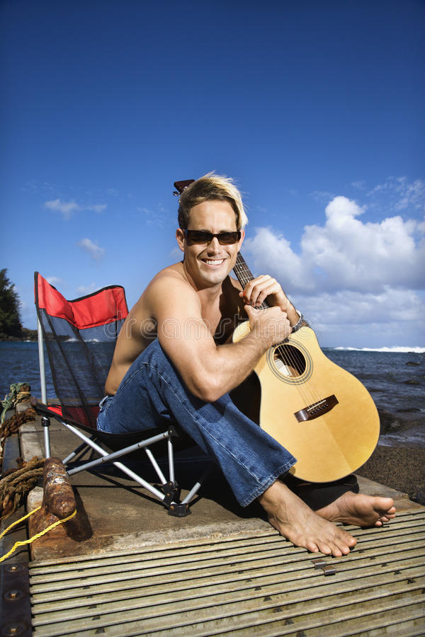 Download Young Man Sitting Lakeside And Holding Guitar Stock Photo - Image: 12755256
