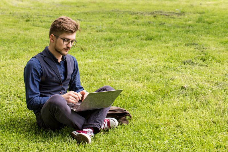 Young man is sitting on a lawn and working on a laptop royalty free stock photos
