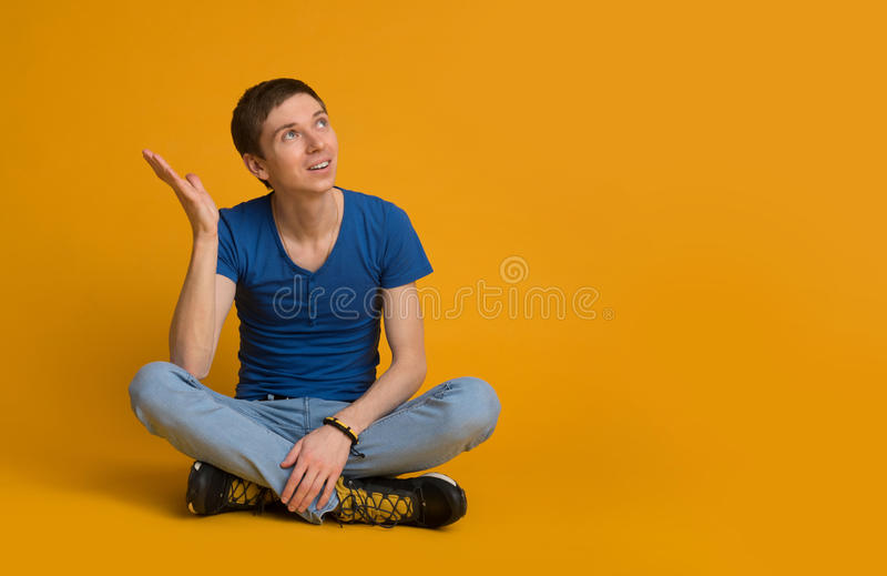 Young man sitting with legs crossed stock images