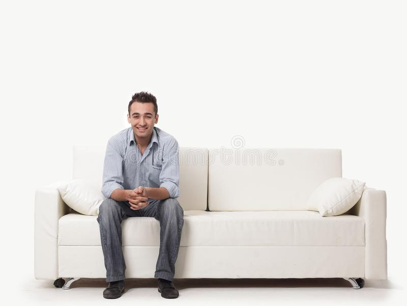 Young man sitting on a modern sofa stock photography