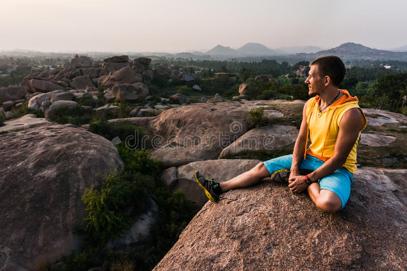 Young man is sitting on the mountain with beautiful view and looking forward. He enjoy sunset stock photos