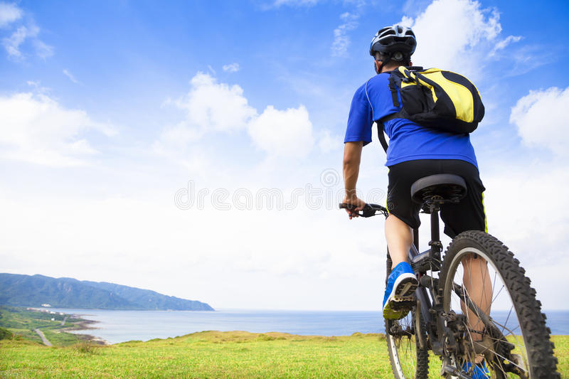 Young man sitting on a mountain bike and looking the ocean. With natural background stock image