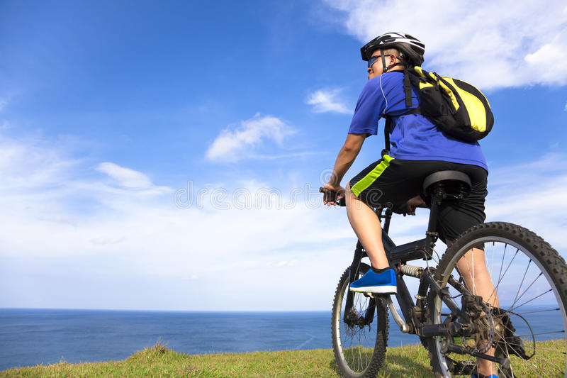Young man sitting on a mountain bike and looking the ocean. In outside royalty free stock image