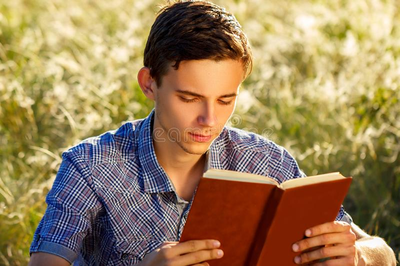 Young man sitting in nature reading a book stock image