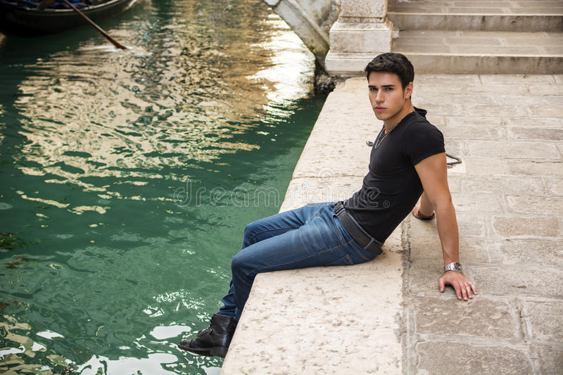 Young Man Sitting Next to Canal in Venice, Italy. Portrait of Attractive Dark Haired Young Man Sitting Docks Next to Narrow Canal in Venice, Italy royalty free stock photos