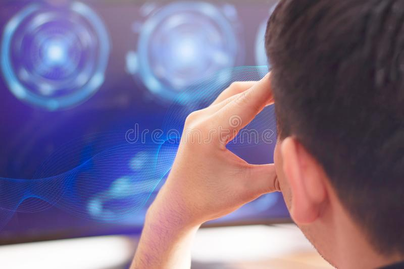 A young man sitting at office computer screen with futuristic sci fi IT digital interface elements and thinking royalty free stock images