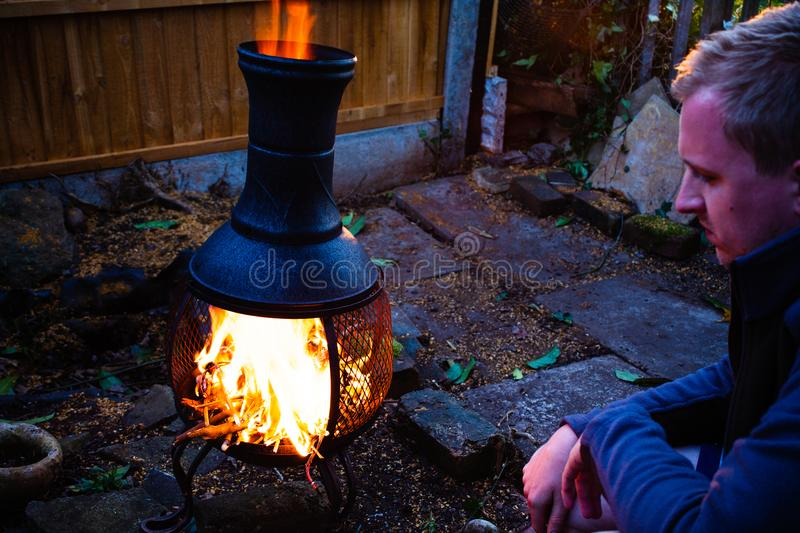 Young man sitting by the open fire in the twilight. Moody photo of man by the camping fire. Outdoor camping concept. Evening by th. Young man sitting by the open royalty free stock image