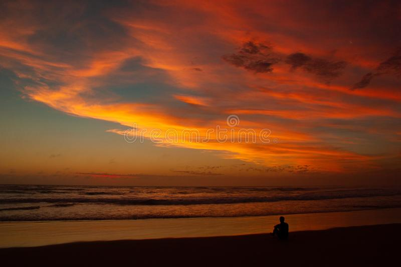 Young man sitting outdoors watching the sunset. Thinking and relaxing concept, Australia. Young man sitting outdoors watching the sunset. Thinking and relaxing stock photo
