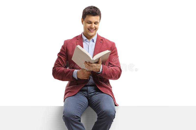 Young man sitting on a panel and reading a book stock photos