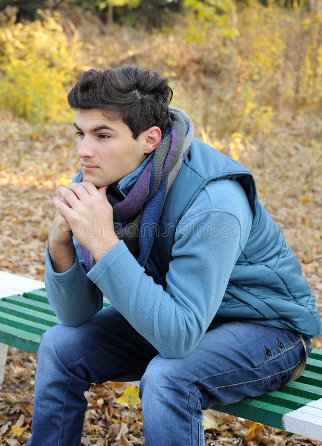 Young man sitting in park. stock image