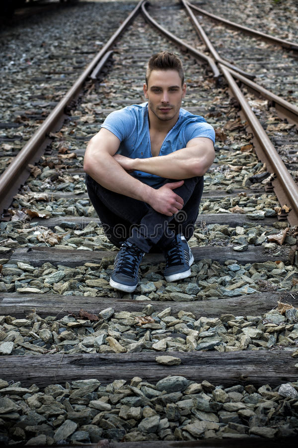 Young man sitting on railroad track royalty free stock photos