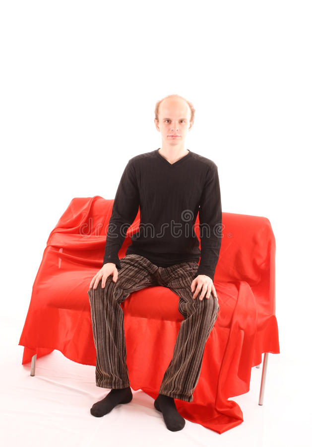 Young man sitting on red sofa isolated stock image