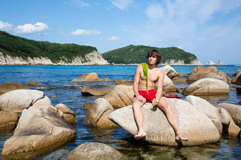 Young man is sitting on a rock stock image