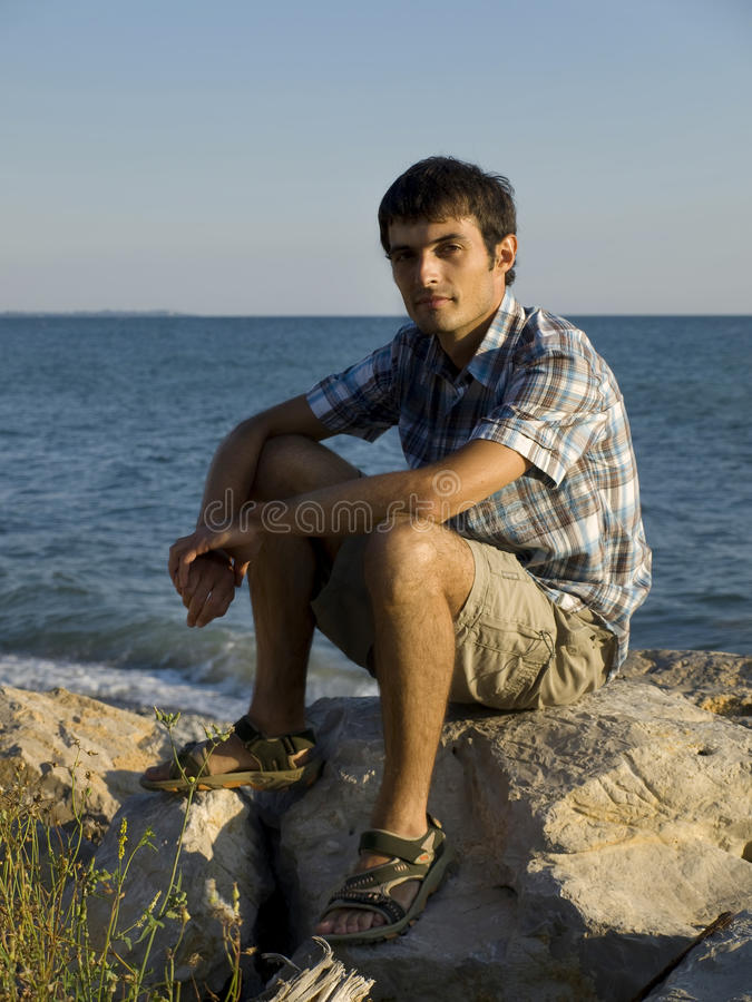 Young man sitting on rocks near sea during sunset stock photo