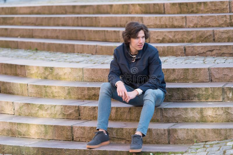A young man is sitting on a stairs outdoors stock photography