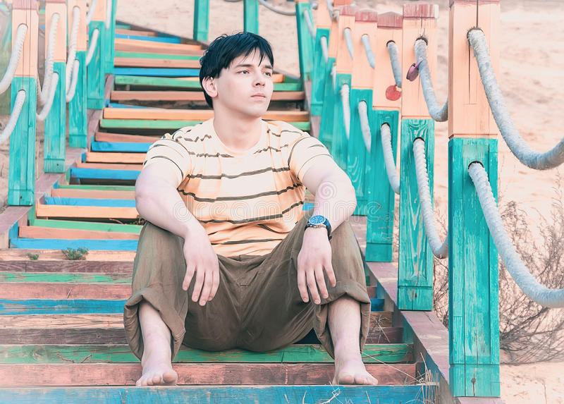 A young man sitting on the steps stock photography