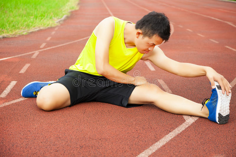 Young man sitting on the track and stretching his leg. Young male runner suffering from knee injury on the track in the stadium royalty free stock images