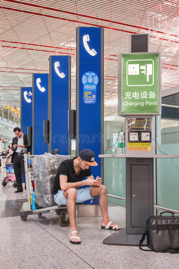 Young man sitting on a trolley, Beijing Capital International Airport. stock photo