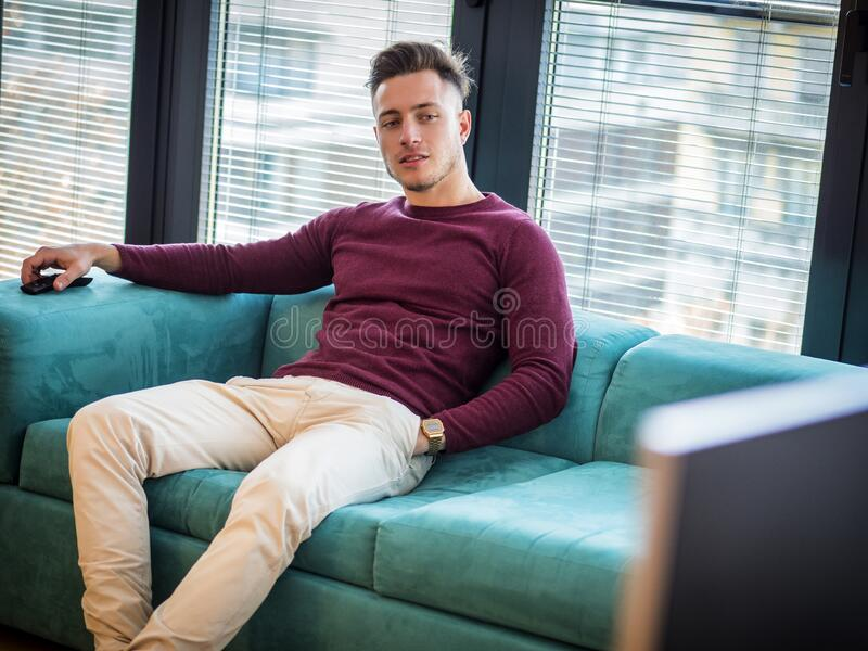 Handsome young man on counch, using TV remote control stock photography