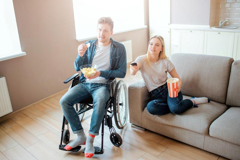 Young man sitting on wheelchair and watching movie with girlfriend. Guy with disability and special needs. Young woman stock photo