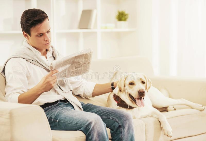 Young Man Sitting on White Sofa with Dog at Home. stock image