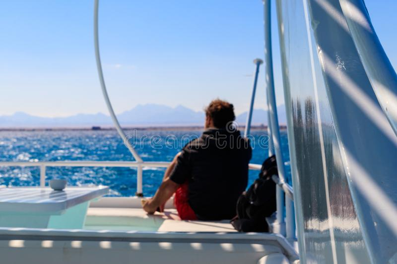 Young man sitting on white yacht and looking at sea or ocean. Luxury vacation concept. Blurred background royalty free stock photography