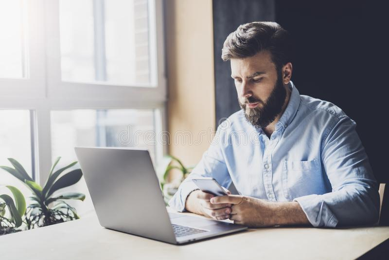 Young man sitting at window and working on laptop. Bearded man sitting at desktop with smartphone in his hands. Online education stock photos