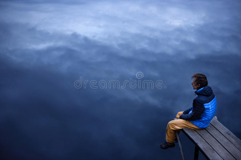 Young man sitting on a wooden dock, looking at skies reflecting. In a lake stock photography