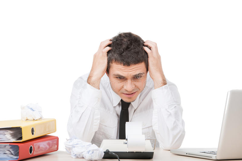 Young man sitting at work and worrying. stock photo