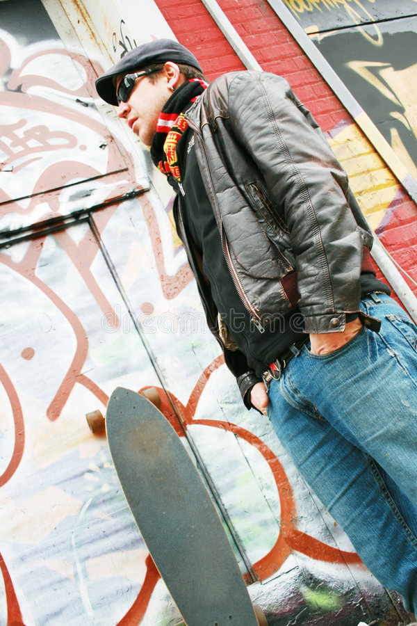 Young man with skateboard. A young man in a cap, jeans and leather jacket stands in front of a skateboard, placed next to a wall covered in graffiti stock image