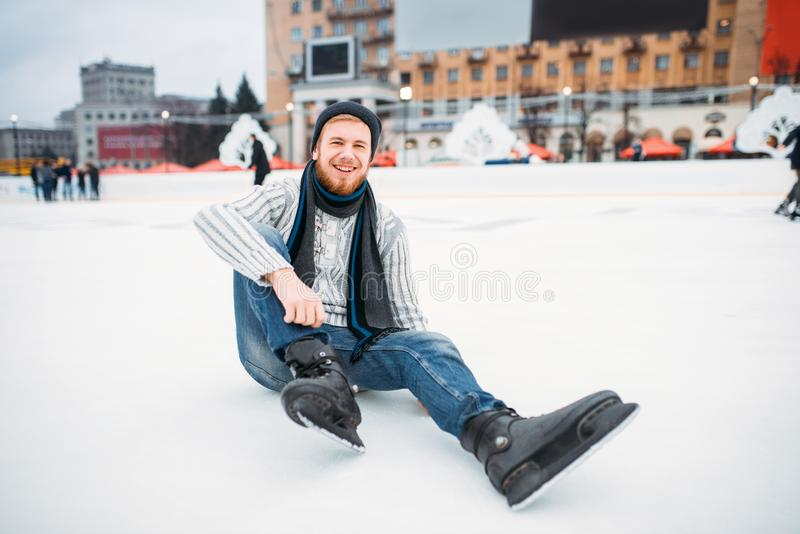 Young man in skates sitting on ice, skating rink. Young smiling man in skates sitting on ice, skating rink. Winter ice-skating on open air, active leisure royalty free stock image