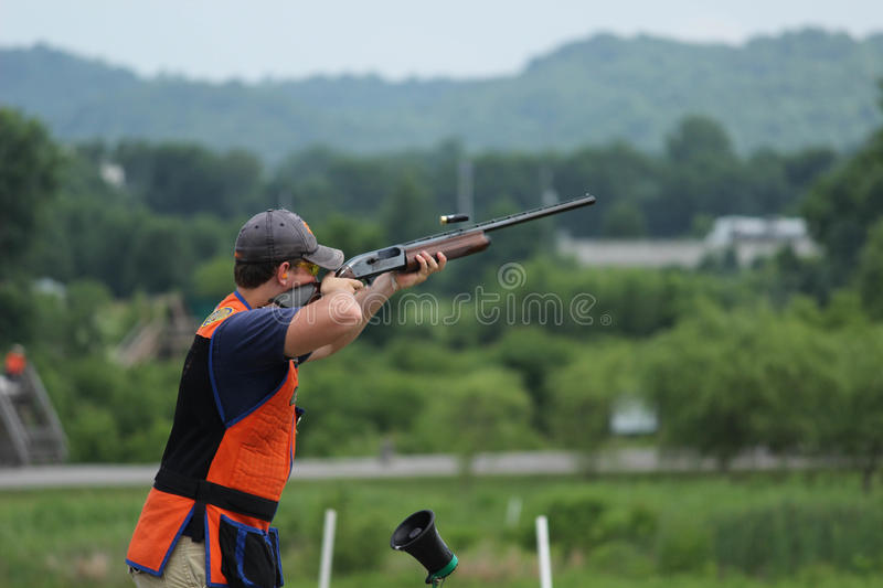 Young man skeet shooting with airborne shell stock photography
