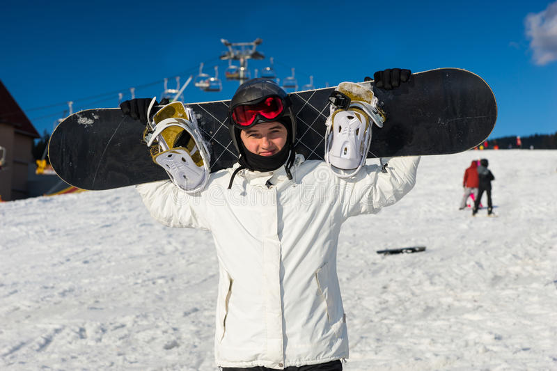 Young man in ski-suit standing and holding his snowboard on his. Young man in ski-suit, helmet and ski goggles standing and holding his snowboard on his royalty free stock photo